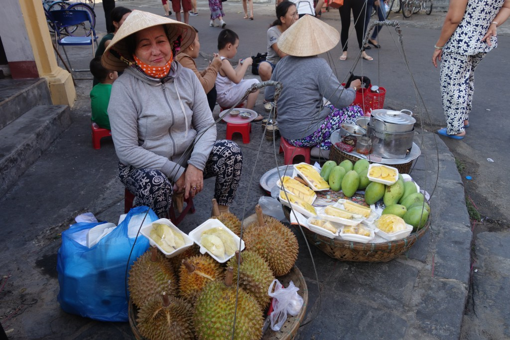 Buying some lobes of durian fruit from a street vendor.