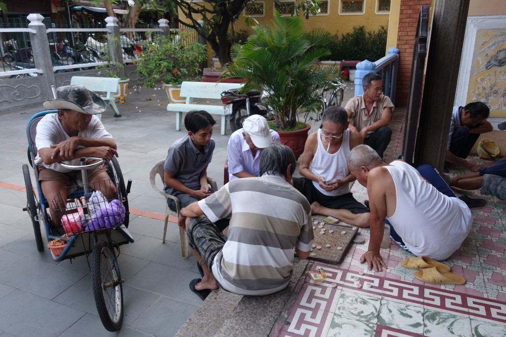 A group playing Chinese chess outside of a temple in Hoi An