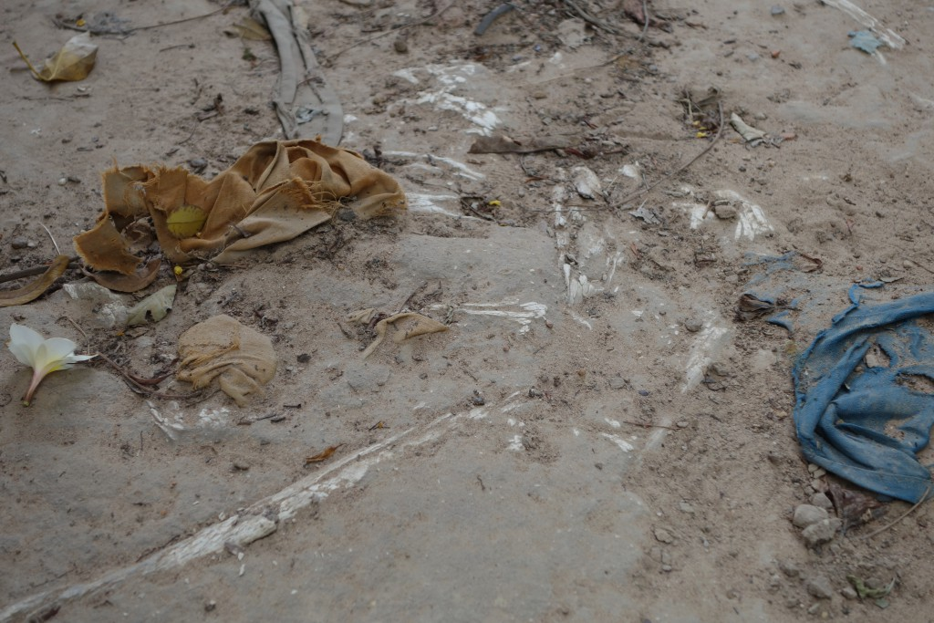 Clothing and bones visible in the soil.
