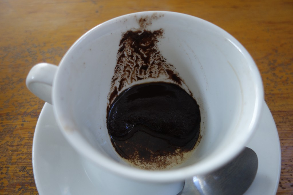 Coffee grounds left at the bottom of a cup.