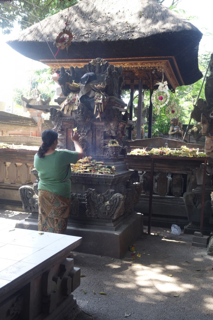 A woman makes an offering at a temple in Ubud.